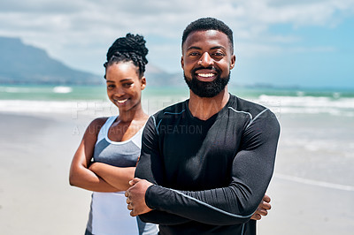 Buy stock photo Portrait of a cheerful young couple standing together with their arms folded on a beach outside during the day