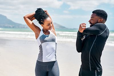 Buy stock photo Cropped shot of a cheerful young couple doing stretching exercises together on a beach outside during the day