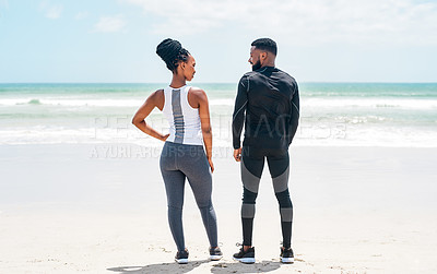 Buy stock photo Rearview shot of a confident young couple looking in each others eyes while standing on a beach outside during the day