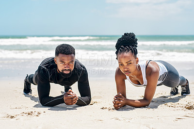 Buy stock photo Shot of a confident young couple doing training exercises together outside on a beach during the day