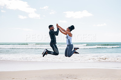 Buy stock photo Shot of a cheerful young couple jumping in the air giving each other a high five outside on a beach during the day
