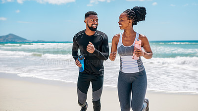 Buy stock photo Cropped shot of a cheerful young couple having a jog together outside on a beach during the day