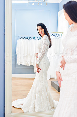 Buy stock photo Cropped shot of a beautiful young bride looking at herself in the mirror while fitting her wedding gown in a bridal shop