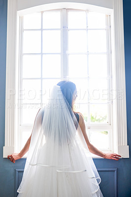 Buy stock photo Rearview shot of a beautiful young bride wearing her wedding gown in her dressing room