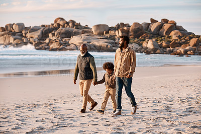 Buy stock photo Shot of an adorable little boy going for a walk along the beach with his grandfather and father