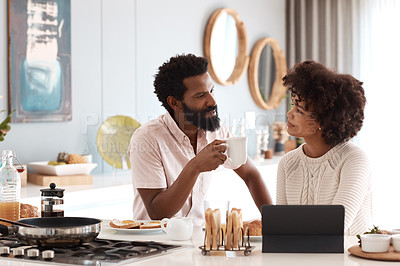 Buy stock photo Shot of a couple using a digital tablet while having breakfast at home