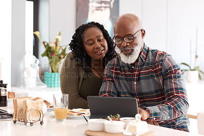 Buy stock photo Shot of a mature couple using a digital tablet while having breakfast together at home