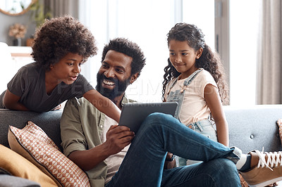Buy stock photo Shot of two adorable young siblings using a digital tablet while bonding and relaxing with their father at home