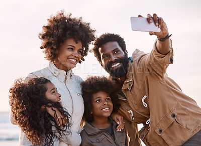 Buy stock photo Shot of a happy young family taking a selfie with a smartphone at the beach