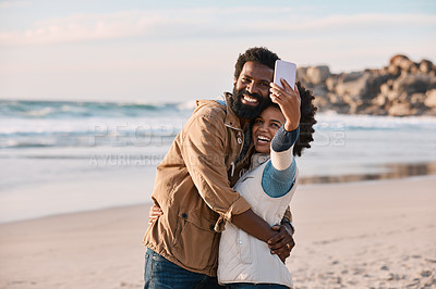 Buy stock photo Shot of a happy young couple taking selfies with a smartphone at the beach