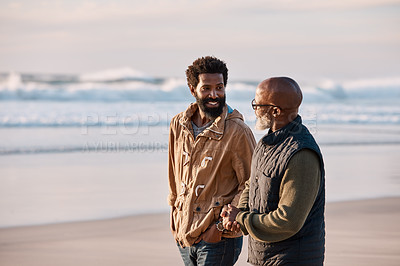 Buy stock photo Shot of a young man going for a walk along the beach with his father