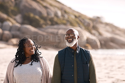 Buy stock photo Shot of a happy mature couple going for a romantic walk along the beach