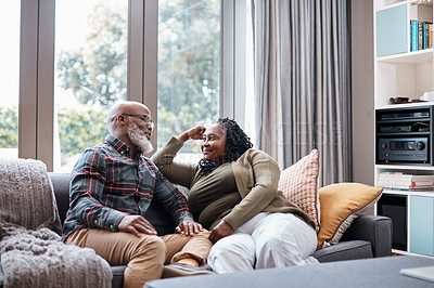 Buy stock photo Shot of a mature couple relaxing together on a sofa at home