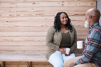 Buy stock photo Shot of a mature couple drinking coffee while having a chat outdoors