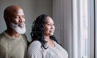 Buy stock photo Shot of a mature couple looking thoughtfully through a window at home
