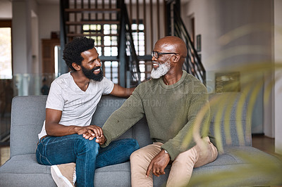 Buy stock photo Shot of a happy young man relaxing and spending time with his father at home