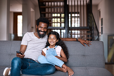 Buy stock photo Shot of an adorable little girl watching tv and spending time with her father at home