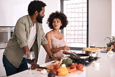 Buy stock photo Shot of a man talking to his wife while she cooks