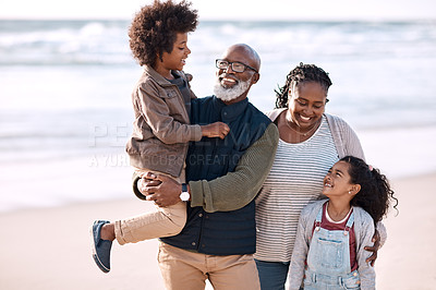 Buy stock photo Shot of an adorable little boy and girl spending time with their grandparents at the beach