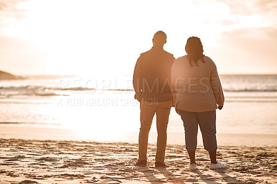 Buy stock photo Rearview shot of a happy mature couple watching the sunset at the beach
