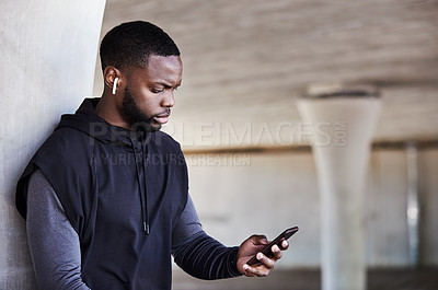 Buy stock photo Cropped shot of a handsome young male athlete checking his phone while working out in the city