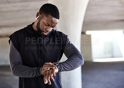 Buy stock photo Cropped shot of a handsome young male athlete checking his watch while working out in the city