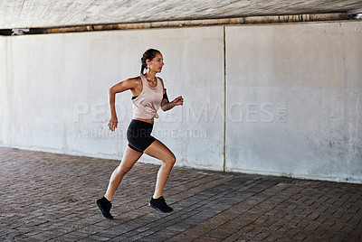 Buy stock photo Full length shot of an attractive young female athlete working out in the city