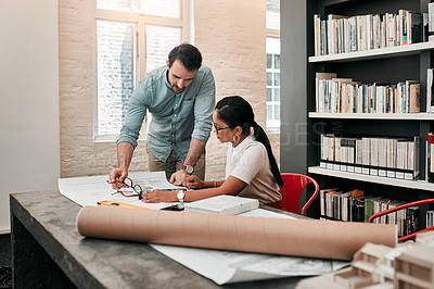 Buy stock photo Cropped shot of two aspiring young architects using a digital tablet while working together in a modern office