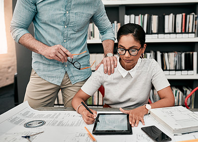 Buy stock photo Cropped shot of an attractive young female architect using a digital tablet while working with her colleague in a modern office