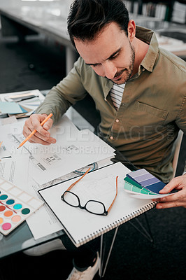Buy stock photo Cropped shot of a handsome young male architect working with some blueprints in a modern office