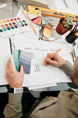 Buy stock photo High angle shot of an unrecognizable male architect working with some blueprints in a modern office