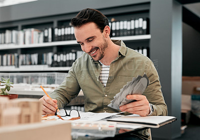 Buy stock photo Cropped shot of a handsome young male architect smiling while working with some blueprints in a modern office