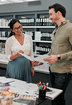 Buy stock photo Cropped shot of two aspiring young architects working with a blueprint in a modern office