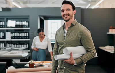 Buy stock photo Shot of a young architect holding rolled up blueprints in an office