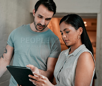 Buy stock photo Cropped shot of two young designers looking at something on a digital tablet