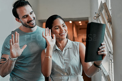Buy stock photo Cropped shot of two young designers using a digital tablet to make a video call