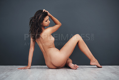 Buy stock photo Studio shot of a gorgeous young woman posing nude against a grey background