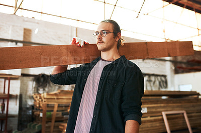 Buy stock photo Shot of a handsome young carpenter carrying a wooden plank over his shoulders inside a workshop