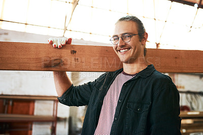 Buy stock photo Portrait of a handsome young carpenter carrying a wooden plank over his shoulders inside a workshop