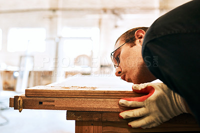 Buy stock photo Shot of a handsome young carpenter blowing dust off a wooden plank inside a workshop