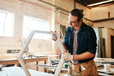Buy stock photo Shot of a handsome young carpenter working on a wooden frame inside a workshop
