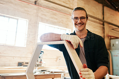 Buy stock photo Portrait of a handsome young carpenter working on a wooden frame inside a workshop