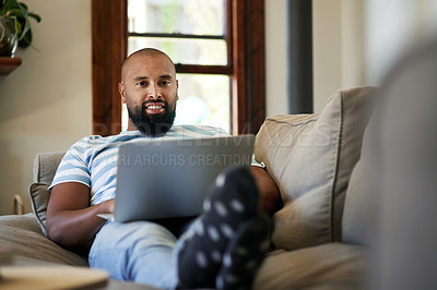 Buy stock photo Portrait of a handsome young man smiling while using a laptop in his living room at home