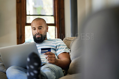 Buy stock photo Cropped shot of a handsome young man using a credit card and a laptop to shop online in his living room at home