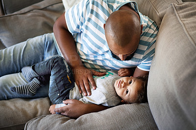 Buy stock photo High angle shot of an affectionate young single father spending time with his little son in their living room at home