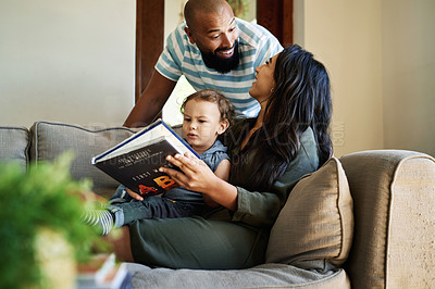 Buy stock photo Cropped shot of an affectionate young couple laughing with each other while reading a picture book with their little son at home