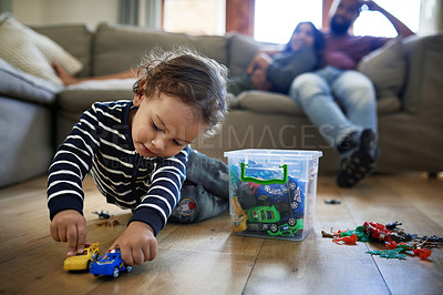 Buy stock photo Full length shot of an adorable little boy playing with his toy cars at home with his parents in the background