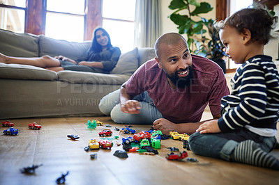 Buy stock photo Full length shot of an affectionate young father playing with his son at home with his wife sitting in the background