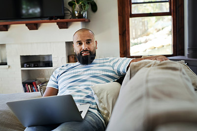 Buy stock photo Cropped portrait of a handsome young man using a laptop while relaxing in his living room at home