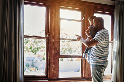Buy stock photo Cropped shot of an affectionate young single father pointing outside while looking through the window with his little son at home